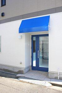 調布市のほほえみ動物病院は、佐須街道から路地に入ってすぐのところに病院の入り口があります。青い屋根と扉が目印です。