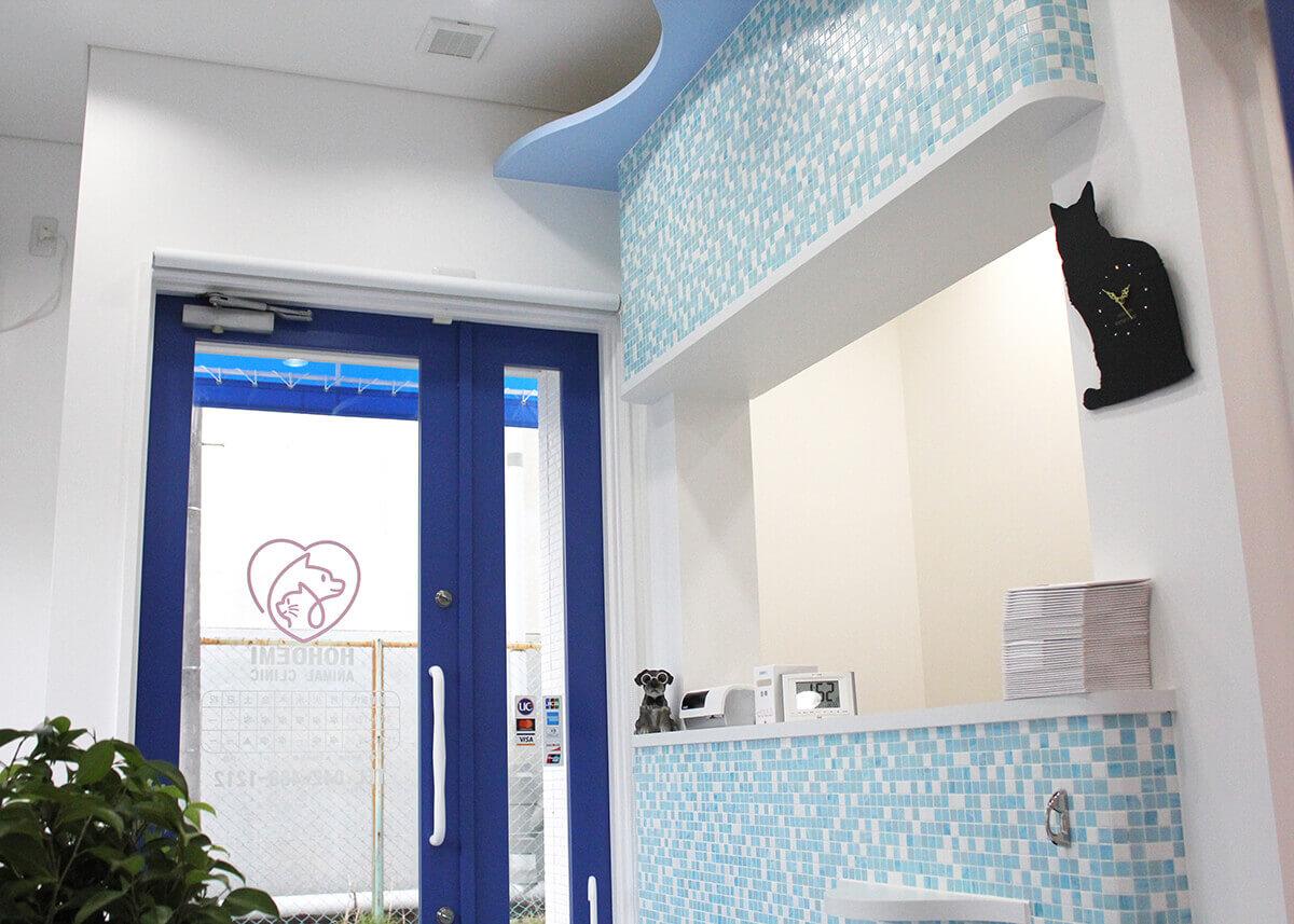 調布・三鷹の動物病院、ほほえみ動物病院の待合室は自然光を取り入れた明るい雰囲気です。海をイメージした曲線と水色とピンクのパステルカラーでリラックスしてお待ちいただけます。